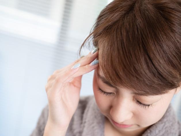 つらい頭痛の症状に悩む女性