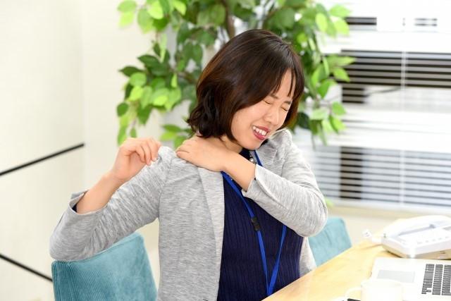 肩の痛みで腕が上がらずに悩む女性
